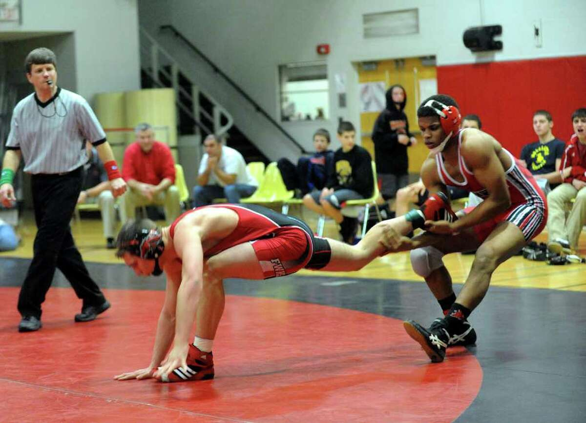 Greenwich's Ryan Whittle grabs a hold of Fairfield Warde's Joey Muratori, during boys wrestling action in Fairfield, Conn. on Wednesday January 11, 2012.