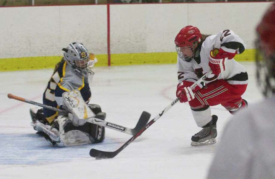 New Canaan's Olivia Hompe moves the puck past Simsbury goalie Dani Sullivan before putting in the goal to score as New Canaan hosts Simsbury in a girls hockey game at the Darien Ice Rink in Darien, Conn., January 11, 2012. Photo: Keelin Daly / Stamford Advocate