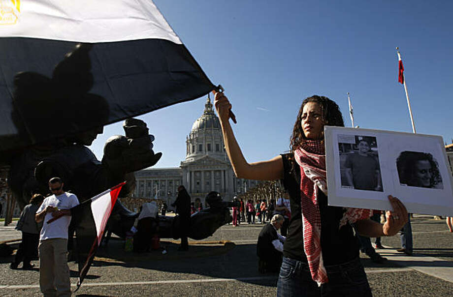 Lena Meari waves an Egyptian flag and holds photos of two protesters, who were among the hundreds killed in Egypt, at Civic Center Plaza in San Francisco on Saturday. The rally was called to remember those who died during the revolution in Egypt, which ultimately led to the resignation of President Hosni Mubarak. Those in attendance observed a moment of silence before the names of the dead were read aloud. Photo: Paul Chinn, The Chronicle