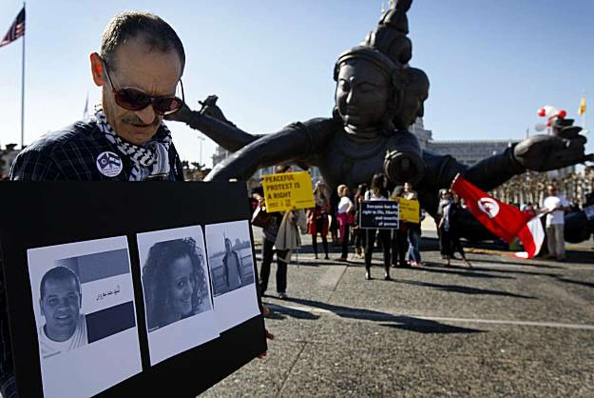 Fayez Hilal displays photos of protesters, who were among the hundreds killed in Egypt, at Civic Center Plaza in San Francisco on Saturday. The rally was called to remember those who died during the revolution in Egypt, which ultimately led to the resignation of President Hosni Mubarak. Those in attendance observed a moment of silence before the names of the dead were read aloud.