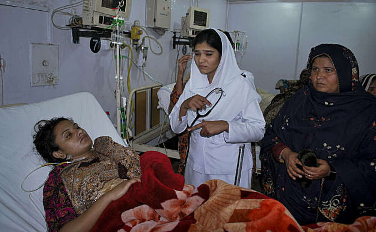 A Pakistani nurse and unidentified relatives of Shumaila Kanwal, bottom, the widow of a Pakistani man allegedly shot and killed by a U.S. official, stand beside her at a local hospital in Faisalabad, Pakistan Sunday, Feb. 6, 2011. Kanwal,tried to commit suicide by eating rat poison Sunday, saying she was driven to act by fears that the American would be freed without trial.