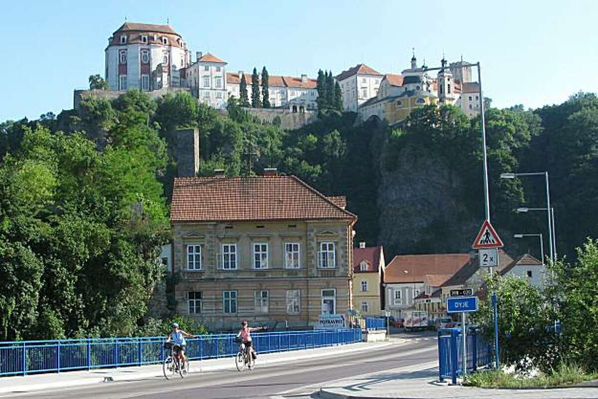 Cyclists enter the Czech town of Vranov nad Dije, in the shadow of the 11th century Vranov chateau.