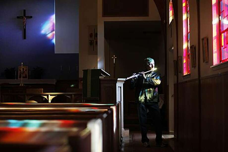 Insisting he was too self conscious the stand for a standard portrait, Larry Kassin, founder and producer of the Noe Valley Music Series, plays jazz and blue flute tunes during a portrait session in the St Cyprians Church on Wednesday January 19, 2011 in San Francisco, Calif. The concert series that got its start 30 years is finding temporary refuge at the church after its old location undergoes renovations. Photo: Mike Kepka, The Chronicle