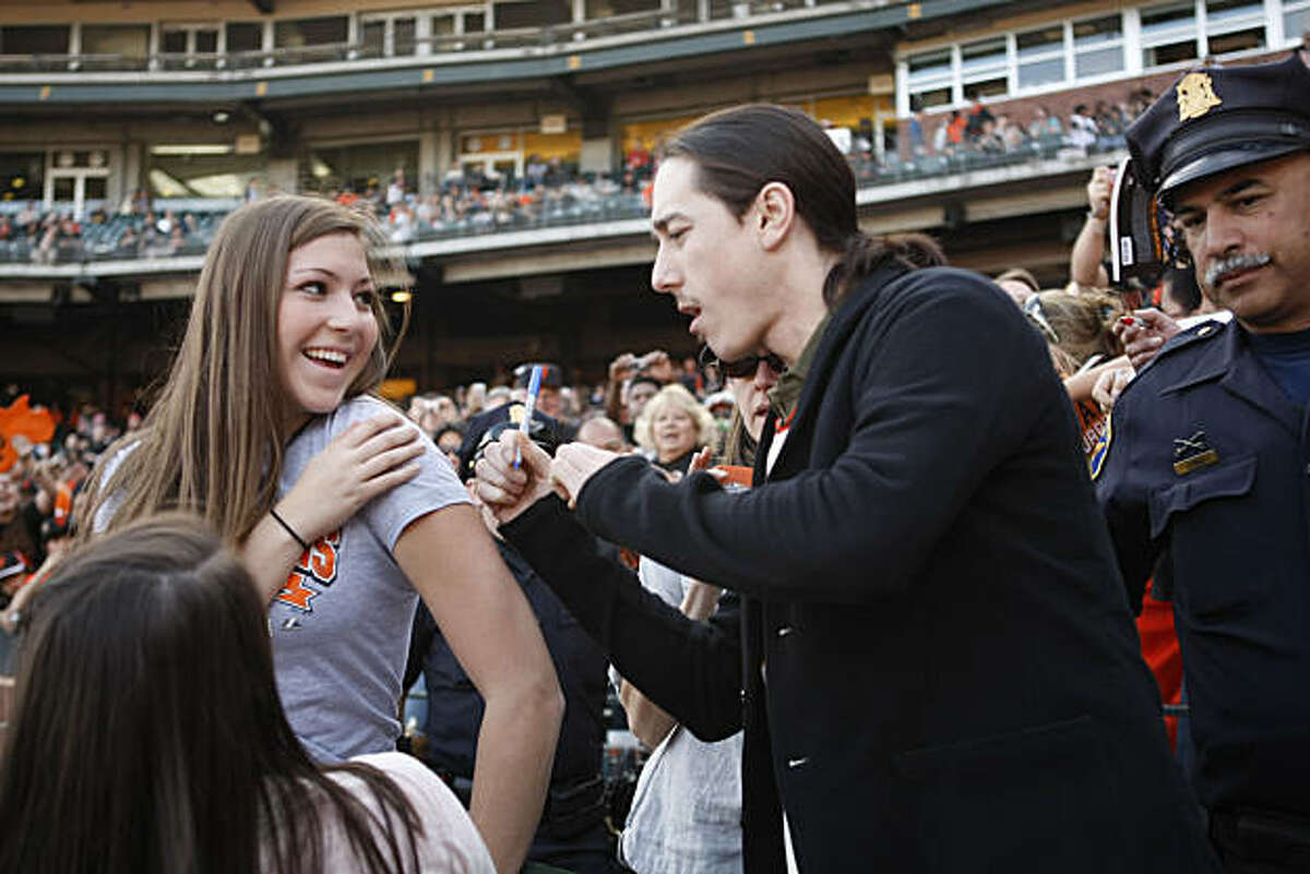Talia Fusara smiles as Tim Lincecum signs the shoulder of her shirt during FanFest at AT&T Park in San Francisco Calif. on Saturday, Feb. 5, 2011.