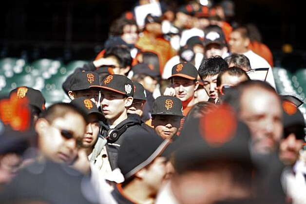 A sea of fans wearing Giants hats wait for autographs. Photo: Anna Vignet, The Chronicle