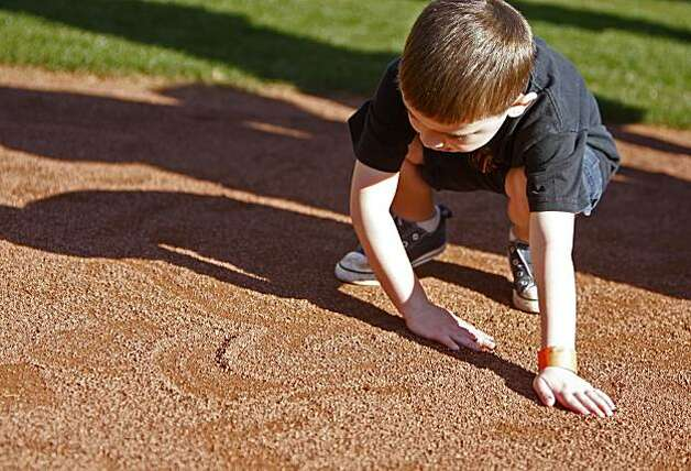 Brody Rhodes, 4, of San Anselmo, plays with the sand on the field. Photo: Anna Vignet, The Chronicle