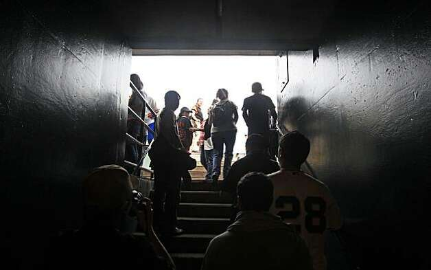 Giants fans walk onto the field through the visiting team's dugout at AT&T Park on Saturday. Photo: Lance Iversen, The Chronicle