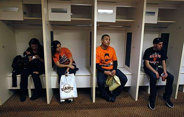 Giants fans take a break and sit in lockers normally occupied by visiting teams at AT&T Park on Saturday. For FanFest, memorabilia was displayed on the walls of the locker room. Photo: Lance Iversen, The Chronicle