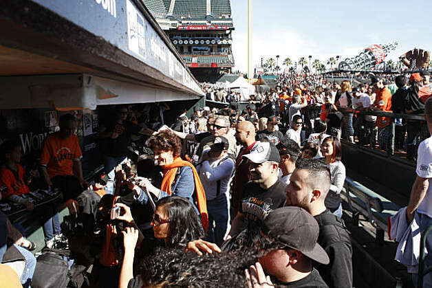 Fans crowd into the Giants dugout to take photos during FanFest at AT&T Park in San Francisco Calif. on Saturday, Feb. 5, 2011. Photo: Alex Washburn, The Chronicle