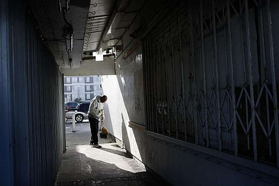 FILE — An unidentified man sweeps the alleyway near the site of a fatal shooting on Monday, Jan. 31, 2011 in San Francisco. A deadly shooting inside a souvenir shop at  Fisherman's Wharf likely stemmed from a business dispute involving another store, police said. Photo: Liz Hafalia, The Chronicle