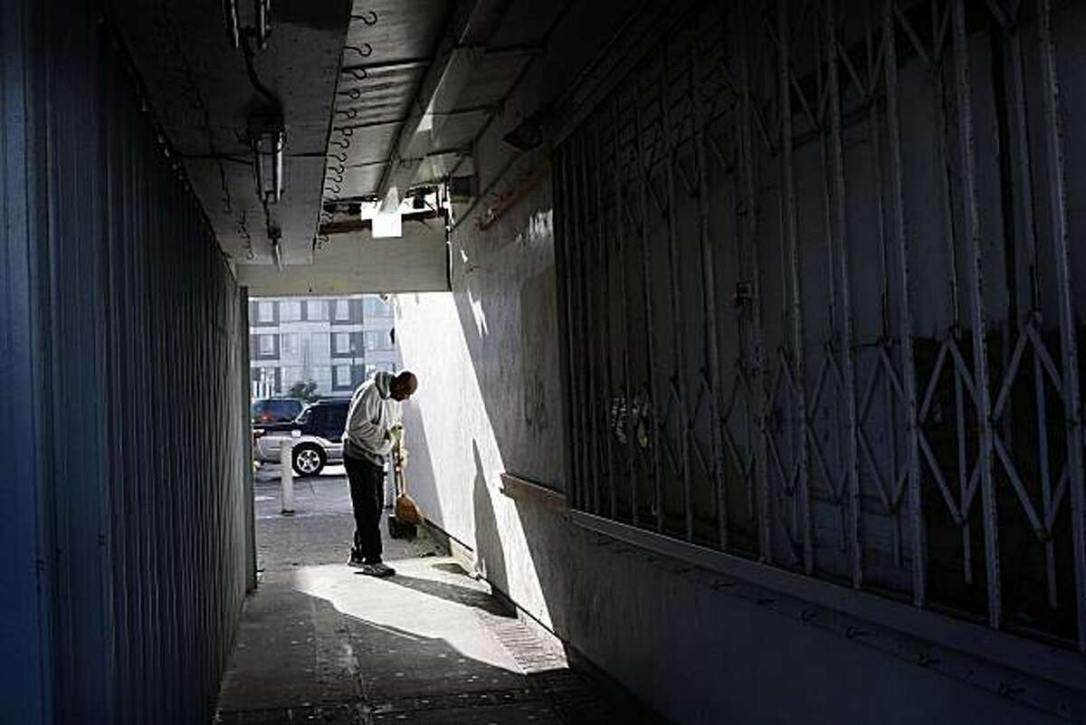 An unidentified man sweeps the alleyway near the site of a fatal shooting on Monday, Jan. 31, 2011 in San Francisco. A deadly shooting inside a souvenir shop at Fisherman's Wharf likely stemmed from a business dispute involving another store, police said. Hong Ri Wu, 56, was arrested for investigation of murder after two store employees were killed Sunday night, investigators said. (AP Photo/San Francisco Chronicle, Liz Hafalia) NO SALES; MAGS OUT; TV OUT; INTERNET OUT; MANDATORY CREDIT
