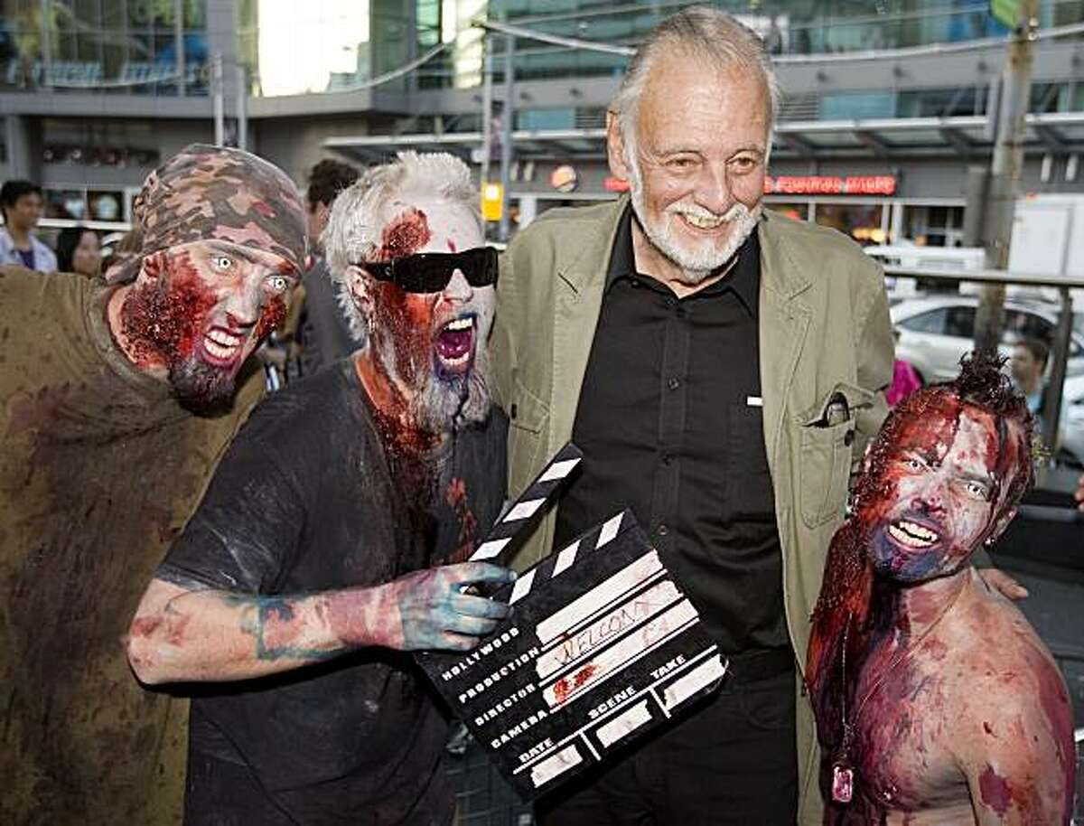 """Director George Romero poses with some fans dressed as zombies after accepting a special award during the Toronto International Film Festival in Toronto on Saturday, September 12, 2009. Romero, known as the """"Godfather of the Dead"""" is set to appear at CTHorrorfest."""