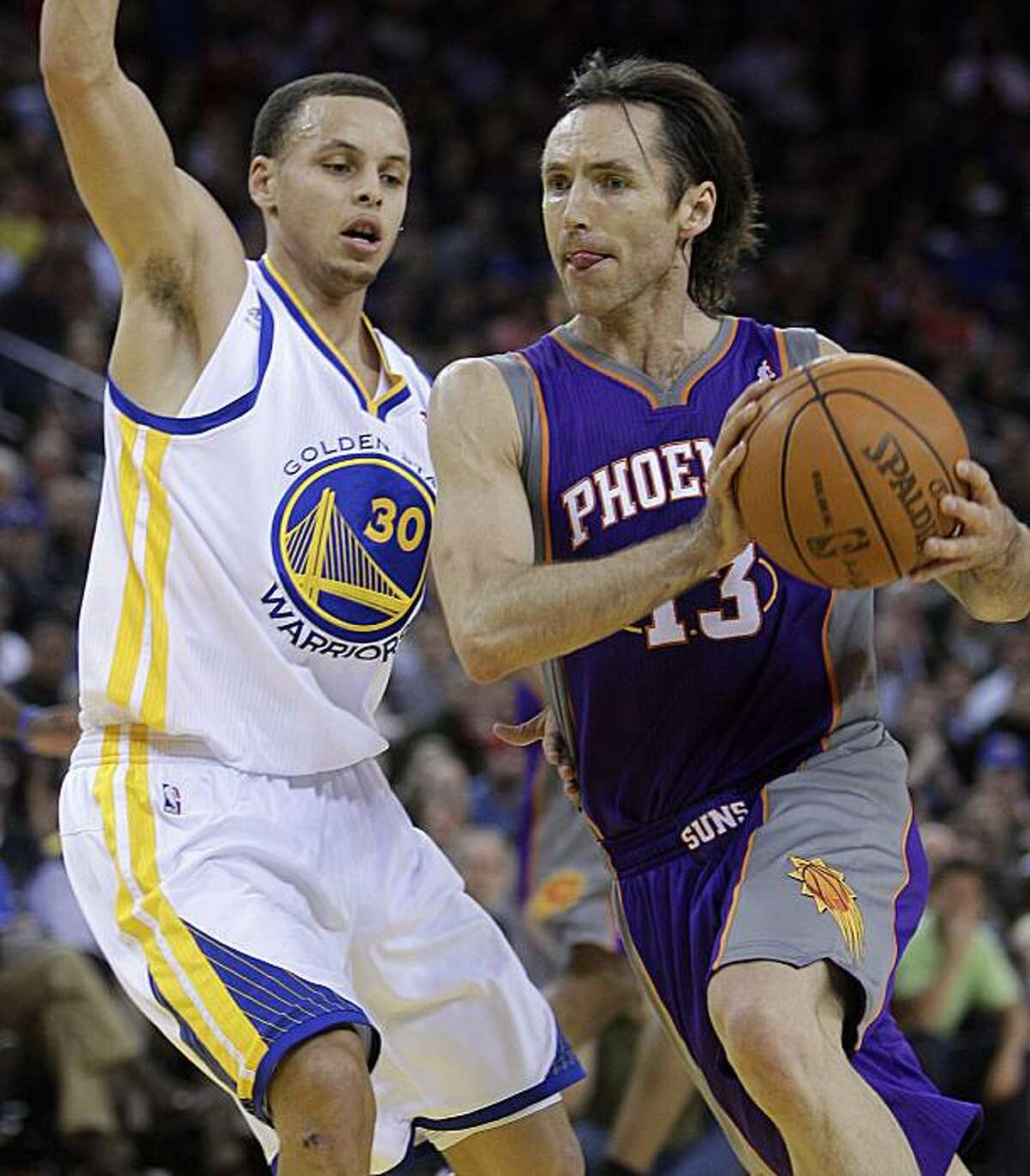 Phoenix Suns' Steve Nash, right, drives to the basket as Golden State Warriors' Stephen Curry defends during the first half of an NBA basketball game Monday, Feb. 7, 2011, in Oakland, Calif.