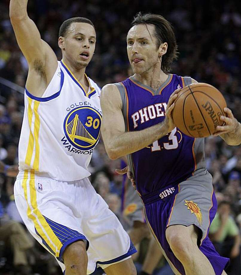 Phoenix Suns' Steve Nash, right, drives to the basket as Golden State Warriors' Stephen Curry defends during the first half of an NBA basketball game Monday, Feb. 7, 2011, in Oakland, Calif. Photo: Ben Margot, AP