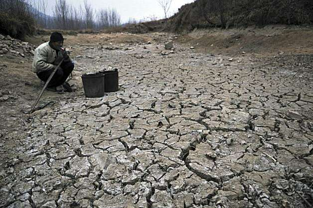 In this photo taken Friday Jan. 28, 2011, a Chinese farmer smokes near a dried up pond in the village of Danuanzhang in Rizhao in eastern China's Shandong province. Months of dry weather have given China's key wheat-growing province of Shandong its worst drought in at least 40 years. That threatens to put further pressure on surging food prices. (AP Photo) CHINA OUT Photo: AP
