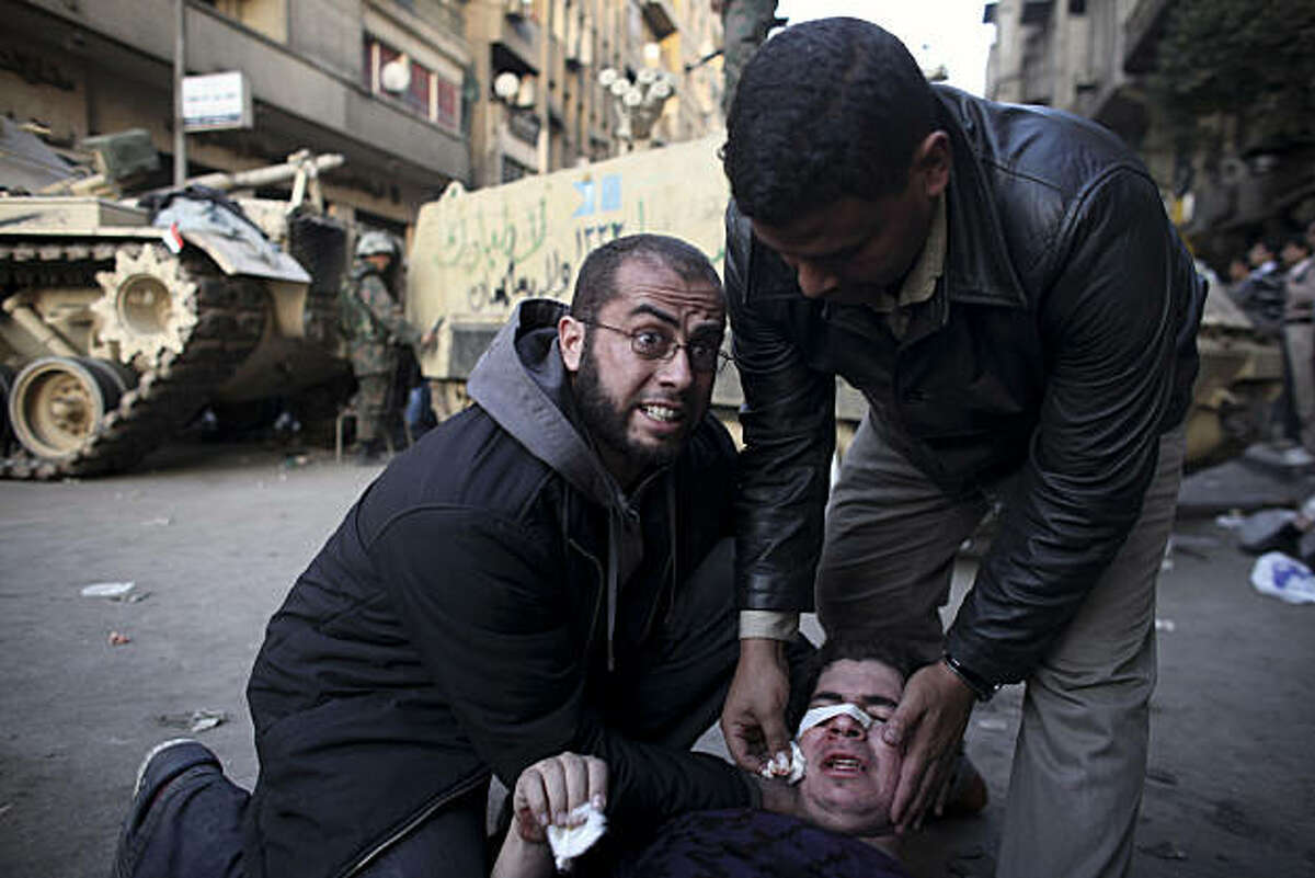 An injured anti-government protester is administered first aid in front of army vehicles during clashes in Tahrir, or Liberation square, in Cairo, Egypt, Wednesday, Feb. 2, 2011. Several thousand supporters of President Hosni Mubarak clashed with anti-government protesters as Egypt's upheaval took a dangerous new turn.