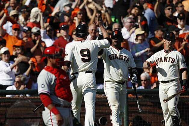 San Francisco Giants' Pat Burrell high fives Juan Uribe after scoring on an RBI single by Aubrey Huff during Game 3 of the National League Championship Series against the Philadelphia Phillies at AT&T Park on Tuesday, October 19, 2010 in San Francisco, Calif. Photo: Carlos Avila Gonzalez, The Chronicle