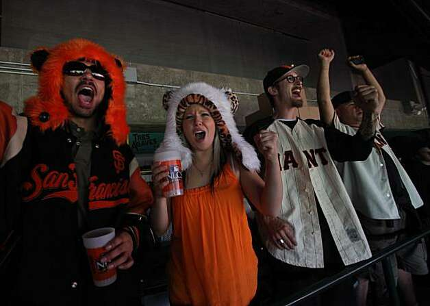 Jeremy Friend, Brittany Strohmayer and Oliver Black of San Francisco, cheer from behind 3rd base during game 3 of the National League Champion series with the San Francisco Giants and the Philadelphia Phillies on Tuesday Nov. 19, 2010 in San Francisco, Calif. Photo: Mike Kepka, The Chronicle
