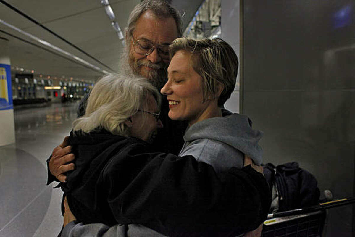 Tonia and John Widler greet their daughter Dawn Lukas, when she returned from Egypt, with smiles and hugs at the San Francisco International Airport, Tuesday Feb. 1, 2011, in San Francisco, Calif. Lukas went to Cairo to teach English, but ended up staying only six days because of the protests.