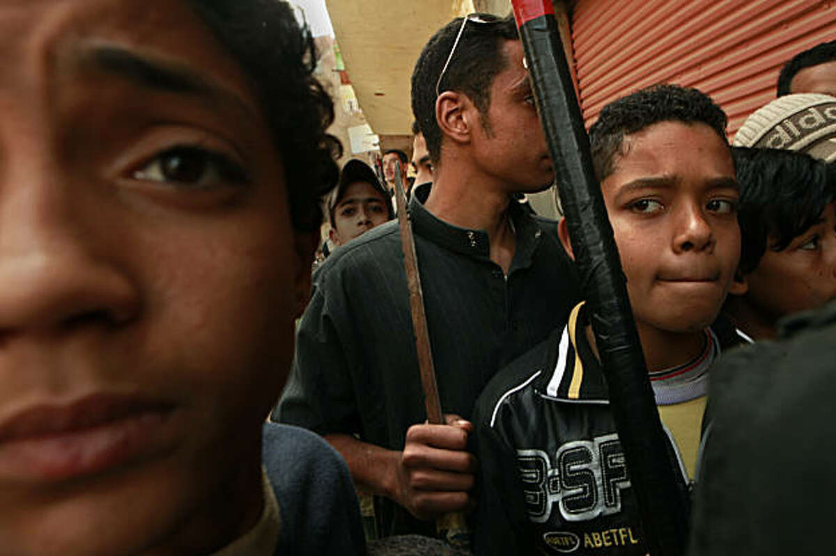 Across the country, Egyptians are taking up arms to protect their neighborhoods, including children yeilding bats and swords. In a poor section of the city of Suez, outsiders are questioned, January 31, 2011. (Carolyn Cole/Los Angeles Times/MCT)