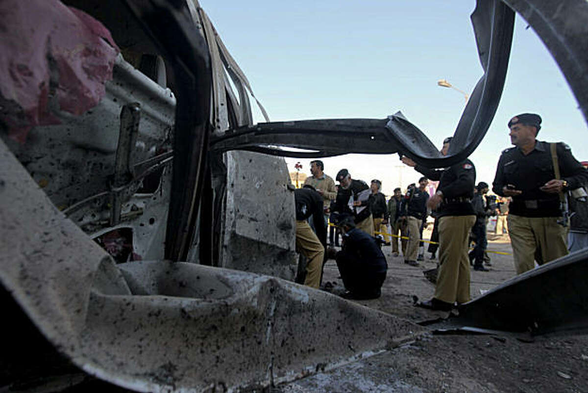 Pakistani police officers examine a damaged vehicle caused by a suicide bombing in Peshawar, Pakistan on Monday, Jan. 31, 2011. A suicide car bomber attacked a vehicle carrying a senior Pakistani police official in the northwestern city of Peshawar on Monday, killing him and two others, said police.