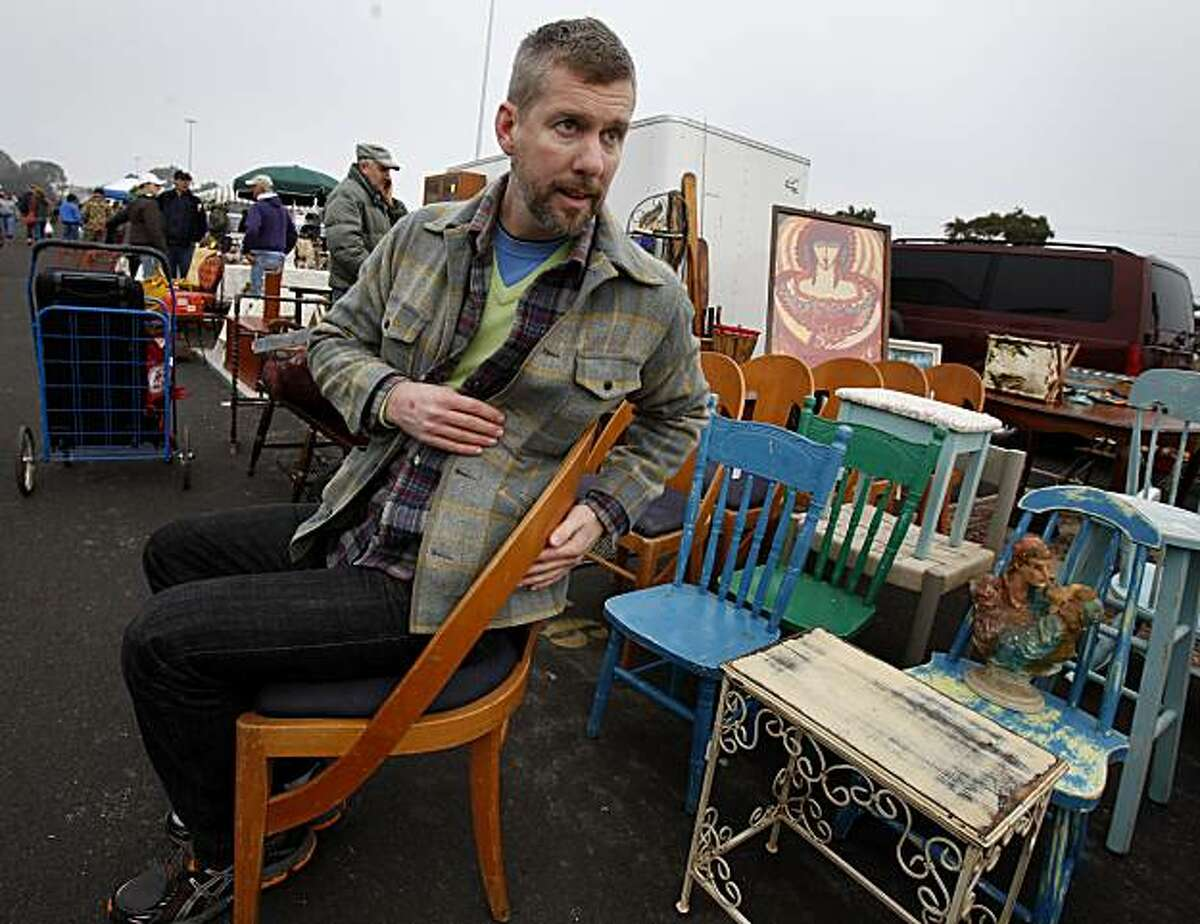 Rob Delamater tries out a set of chairs he likes which will need little refinishing. Shop owner Rob Delamater tours the Candlestick Park Flea Market in search of good finds Sunday January 16, 2011.