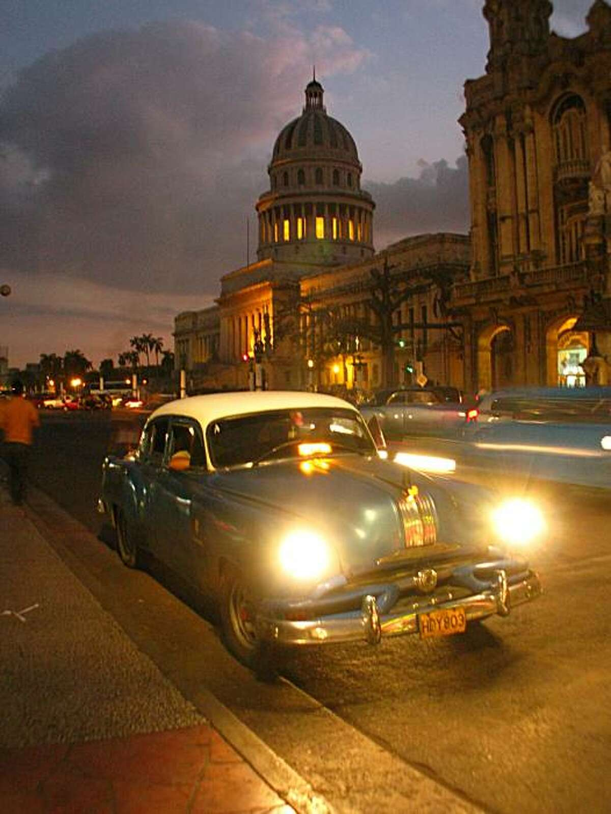 A classic 1950s American car parks for a moment with the Capitolio (the former national capitol building) rising in the background in Havana, Cuba.