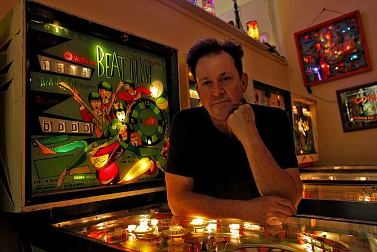 Michael Schiess, who with his wife own the non-profit Pacific Pinball Museum, stands with a game that was designed after the