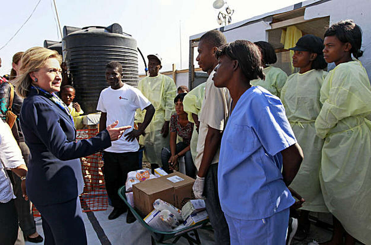 Secretary of State Hillary Rodham Clinton talks with workers as she visits Partners in Health Cholera Treatment Center in Port-au-Prince, Haiti, Sunday, Jan. 30, 2011.