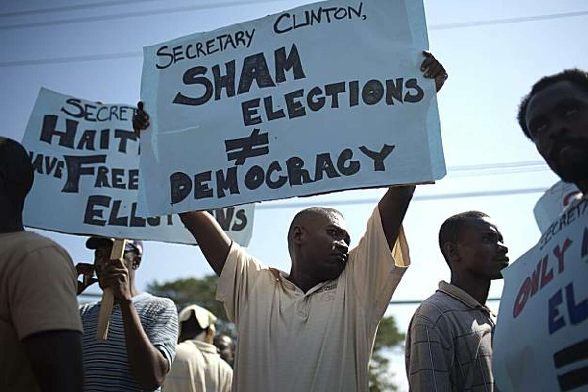 People protest against the visit of Secretary of State Hillary Rodham Clinton, not in picture, outside airport where she arrived in Port-au-Prince, Haiti, Sunday, Jan. 30, 2011. Clinton is scheduled to meet with Haiti's President Rene Preval and each ofthe three presidential candidates jockeying to replace him.