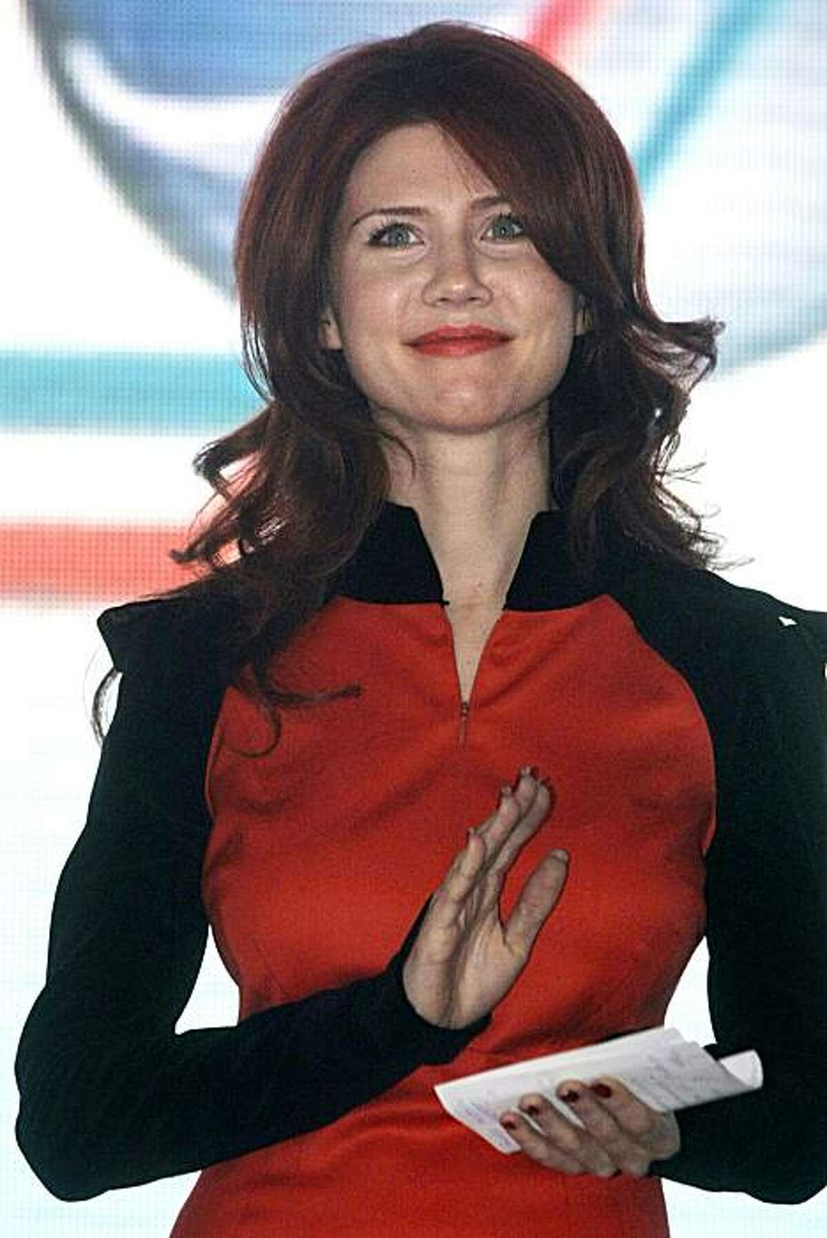 FILE - In this Dec. 22, 2010 file photo, Anna Chapman, who was deported from the U.S. on charges of espionage, is seen on stage during an event with leaders of the Young Guards, a pro-Kremlin youth movement she joined, in Moscow, Russia. Russian spy AnnaChapman is enticing viewers to turn into her new television show by promising to reveal