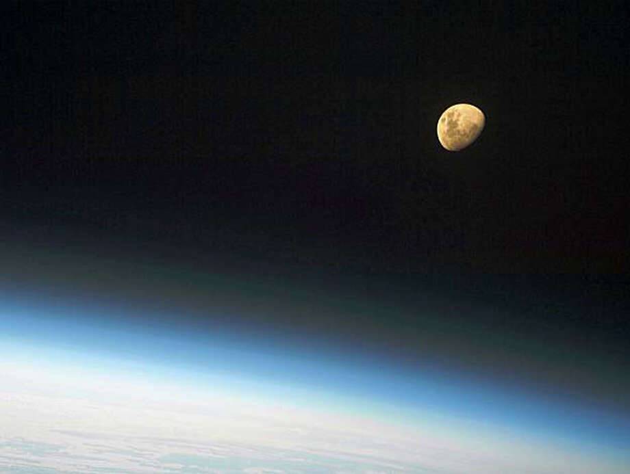 In this image provided by NASA a gibbous moon is visible above Earth's atmosphere, photographed by an STS-128 crew member on the Space Shuttle Discovery Sunday Aug. 30, 2009. A gibbous moon is one of the phases of the Moon, when the size of the illuminated portion is greater than half but not a full Moon.  (AP Photo/NASA) Photo: NASA