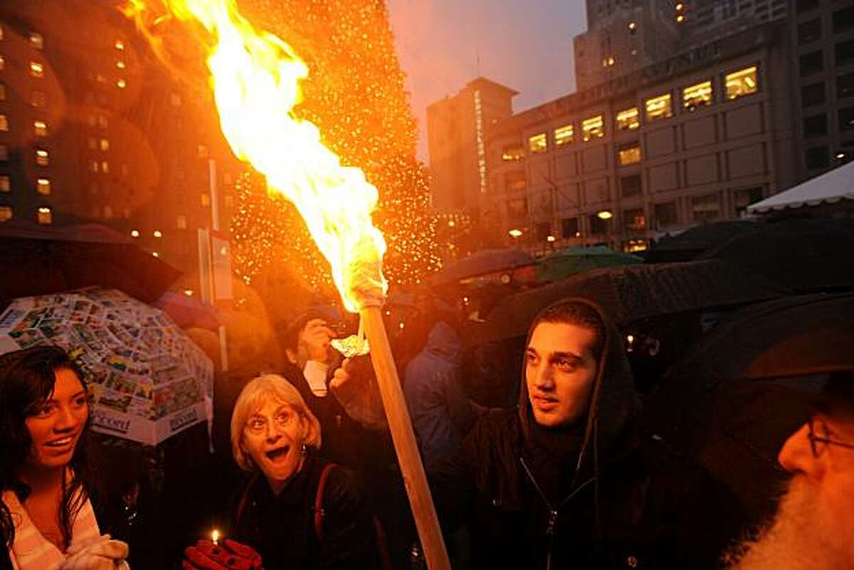 Revelers mark the first night of Hannukah as they light candles off a torch before a Union Square Menorah lighting on Sunday, Dec. 21, 2008, in San Francisco.
