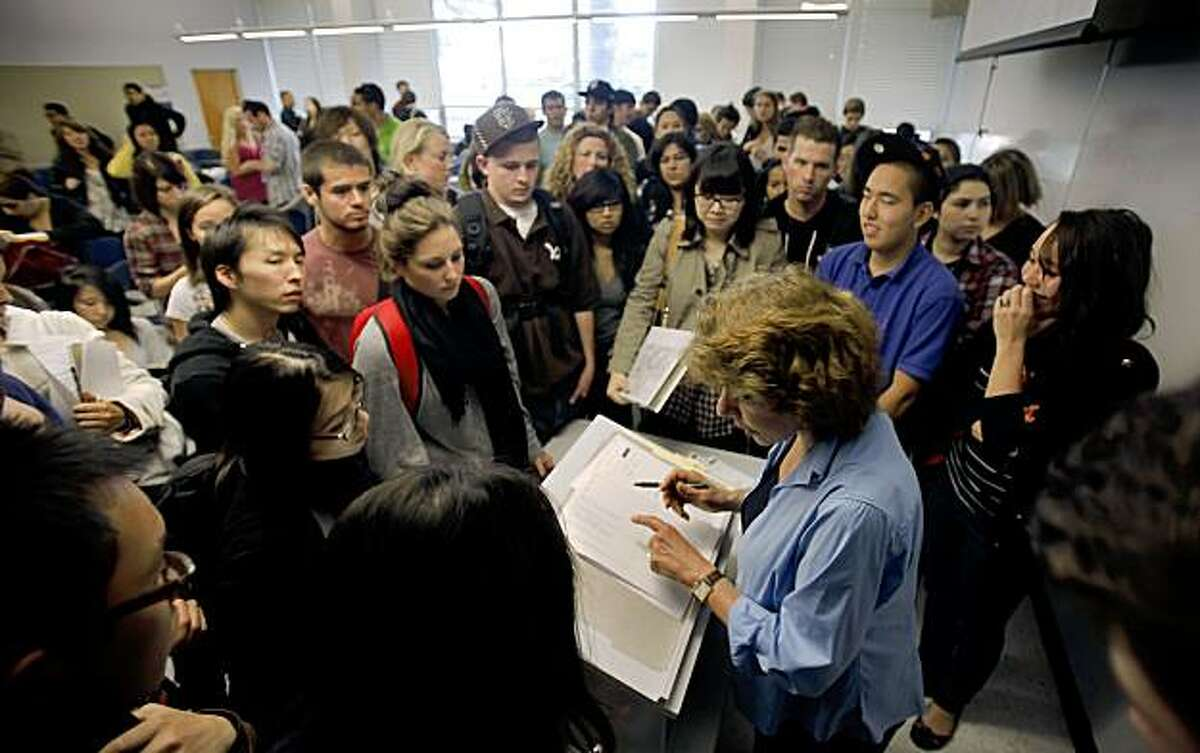 Students crowd around teacher Joanna Moss hoping to enroll in her Economics class at SF State in San Francisco, Calif., on Tuesday, Aug. 25, 2009. Moss, who said cuts in the state budget has forced students to scramble for classes, said attendance was twice as large as usual.