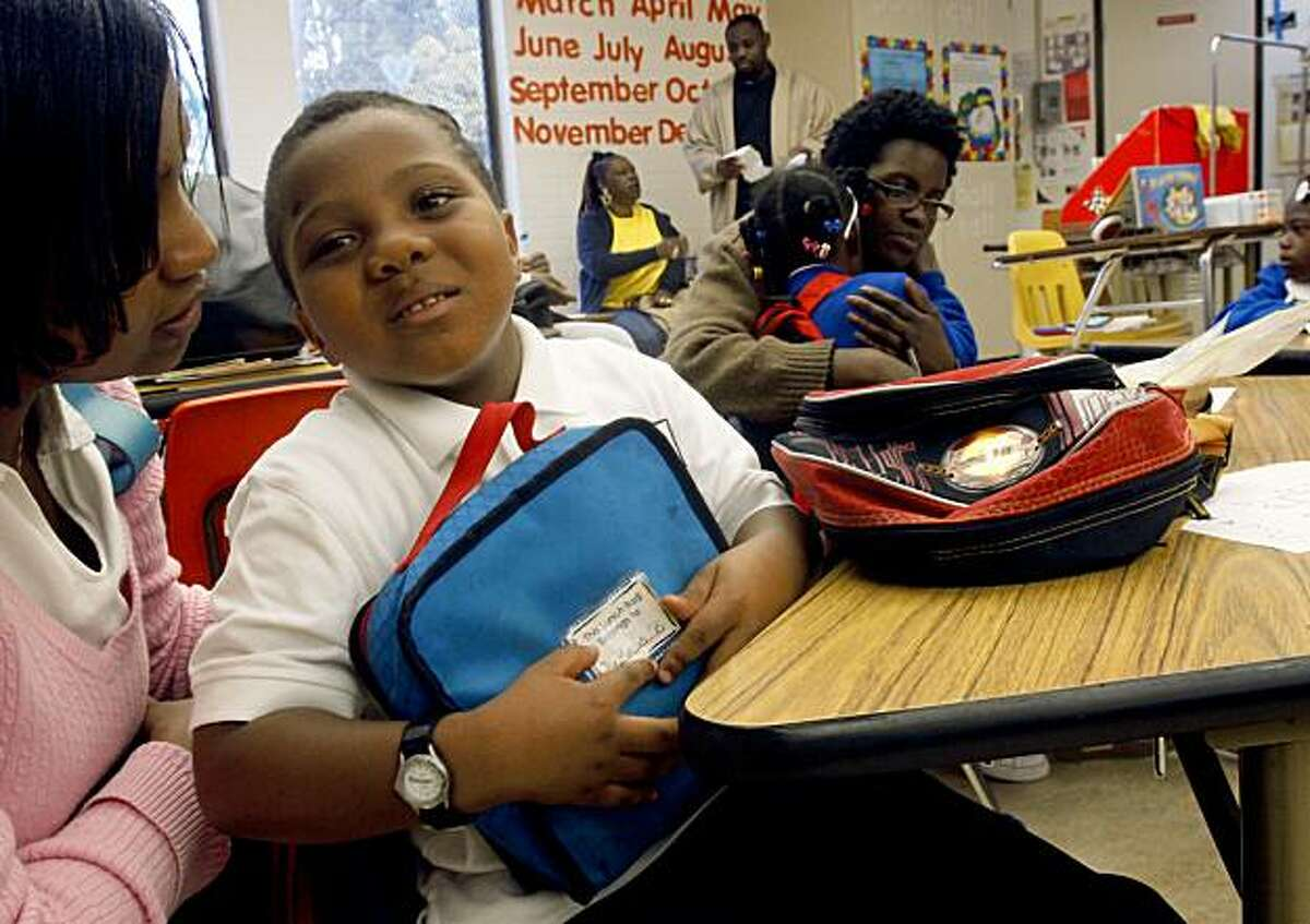 DeMarcus Brown, 5 years old, doesn't want his mom Tamek Tanner(left) to leave as he begins his first day of school at Carver Elementary school in San Francisco, Calif., on Monday, August 24, 2009.