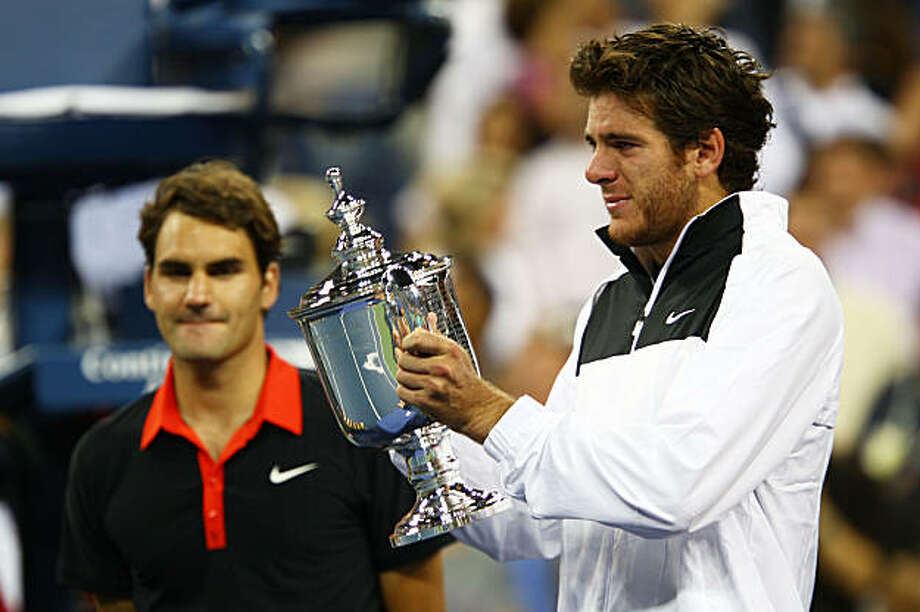 NEW YORK - SEPTEMBER 14:  Juan Martin Del Potro of Argentina holds the championship trophy as Roger Federer of Switzerland looks on in the Men's Singles final on day fifteen of the 2009 U.S. Open at the USTA Billie Jean King National Tennis Center on September 14, 2009 in the Flushing neighborhood of the Queens borough of New York City. Del Potro defeated Federer 3-6, 7-6 (7), 4-6, 7-6 (7), 6-2.  (Photo by Clive Brunskill/Getty Images) Photo: Clive Brunskill, Getty Images