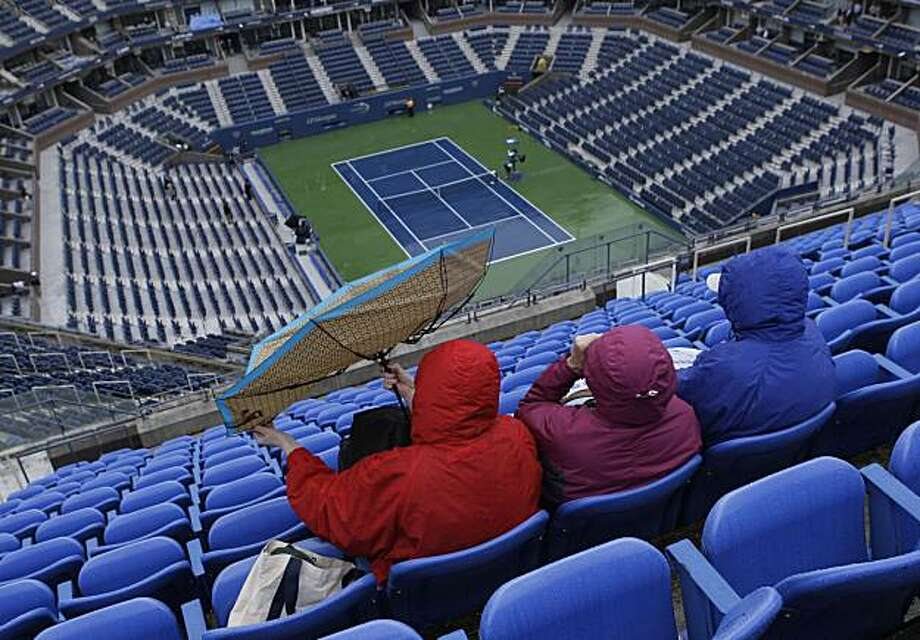 A spectator struggles with her umbrella while waiting for play to begin at the U.S. Open tennis tournament in New York, Friday, Sept. 11, 2009. Play for the day was postponed due to inclement weather. (AP Photo/Charles Krupa) Photo: Charles Krupa, AP