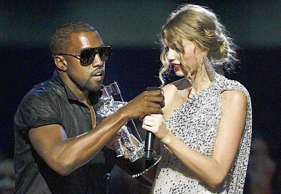 "Singer Kanye West takes the microphone from singer Taylor Swift as she accepts the ""Best Female Video"" award during the MTV Video Music Awards on Sunday in New York. Photo: Jason DeCrow, AP"