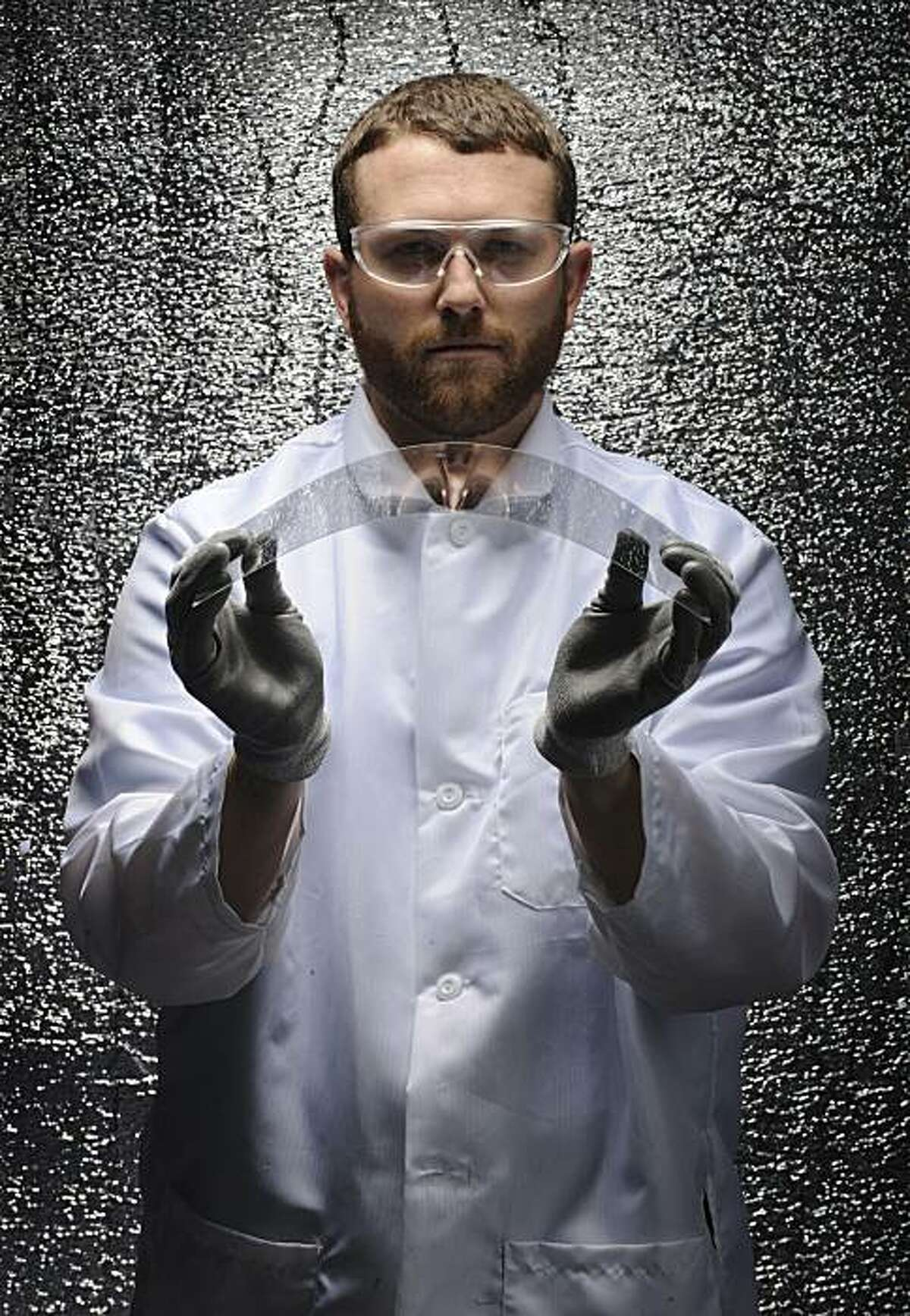FILE - In this undated file photo released by Corning Inc., Corning scientist Matt Black poses for a photo demonstrating the strength and flexibility of Corning's thin and damage resistant Gorilla glass in Corning, N.Y. Corning Inc. said Friday, Feb. 4, 2011, it expects its annual sales to grow more than 50 percent to $10 billion by 2014, driven by surging demand for ultra-thin glass used in television monitors, smart phones and touch-screen tablets.