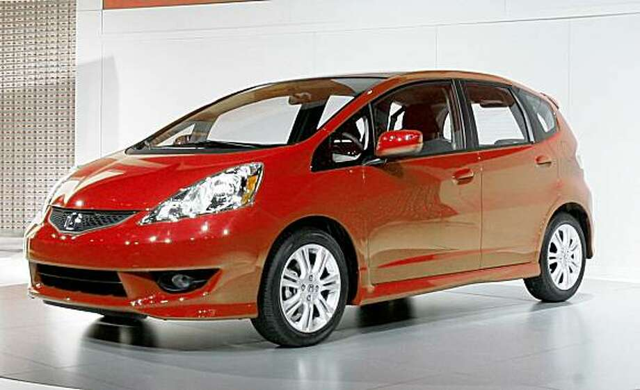 In this March 19, 2008 file photo, the 2009 Honda Fit is introduced during the Honda news conference at the New York International Auto Show. Honda Motor Co. is coming out with hybrid cars that will cost about $1,900 more than a gas-only model. The price for the Detroit Three could be lower market share. Honda's small car and hybrid expertise put the company a step ahead of Detroit and especially Ford and Chrysler, which are still scrambling to sell conventional tiny cars in the United States.  (AP Photo/Mary Altaffer, file) Photo: Mary Altaffer, AP