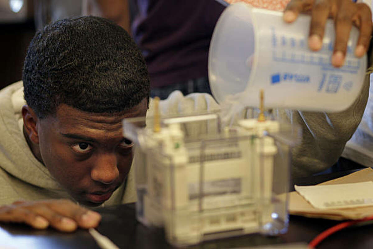 DeLeon Johnson, a senior in the Biotech class at Lincoln High School pours liquid into a Polyacrylamicle Gel Electrophoresis Machine, Tuesday January 25, 2011, in San Francisco, Calif. His class exemplifies the school's focus on science, which emphasizes problem solving and the ability to apply scientific principles.
