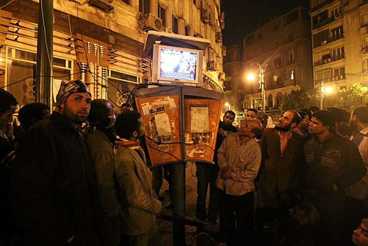 Egyptians gather to watch the Al-Jazeera satellite television station on a set placed on top of public telephone booths in Cairo's Tahrir Square, following a seventh day of protests calling for the removal of President Hosni Mubarak's regime on January 31, 2011.