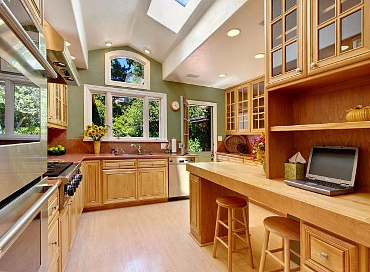 The sunny kitchen has multiple windows, skylights, glass-fronted cabinetry, stainless steel appliances and a breakfast bar.