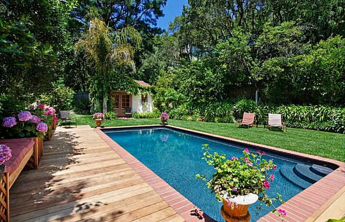 The in-ground swimming pool sits in the backyard between the main house and cabana.