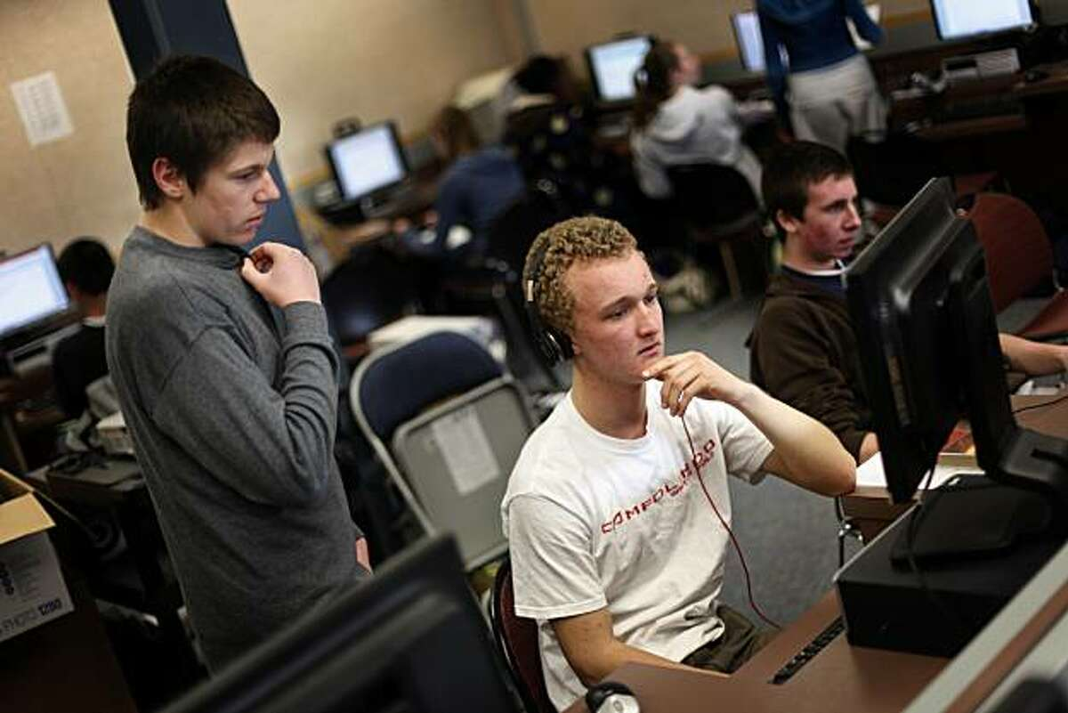 Andy Grubbs (left), junior, consults with Cole Rider (right), junior, as he works on paper during a junior english class at the drop in computer lab at Campolindo High School on Wednesday, January 19, 2011 in Moraga, Calif.