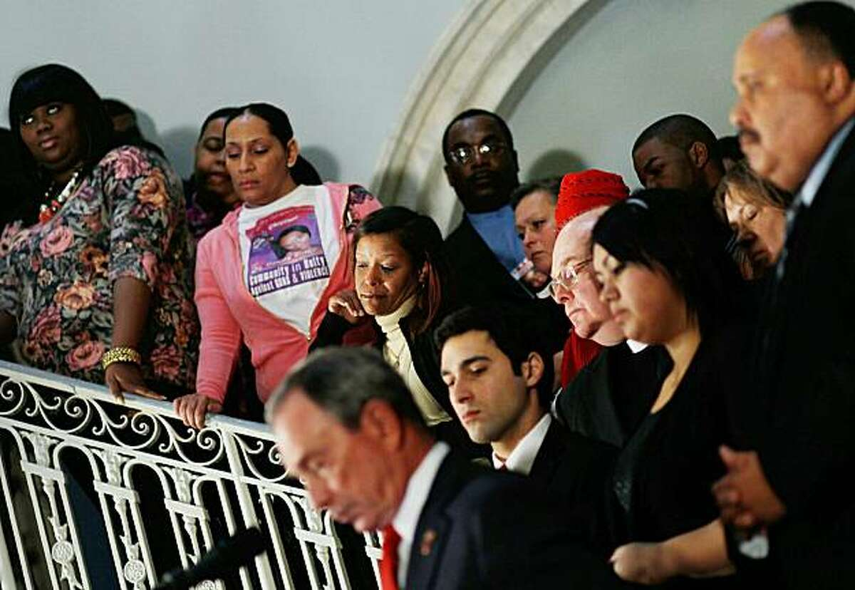 NEW YORK, NY - JANUARY 24: People who had family members killed or injured in gun violence listen to New York City Mayor Michael Bloomberg (bottom) give a speech on gun laws January 24, 2011 in the rotunda of City Hall in New York City. The mayor, speaking along with Martin Luther King III, called for existing gun laws and background checks on the books to be enforced more rigorously and said that 34 American a day are killed in gun-related incidents.