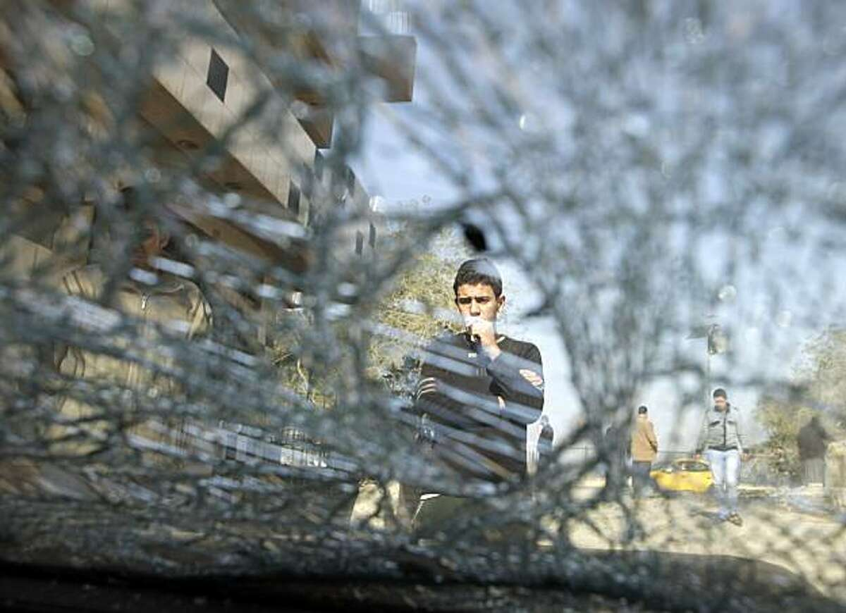 An Iraqi teenager is seen through a shattered car windshield after a bombing in Baghdad, Iraq, Sunday, Jan. 23, 2011. A flurry of morning bombs killed and wounded several across Baghdad Sunday, police said, in what one Iraqi official called an attempt toundermine security ahead of a much anticipated meeting of Arab heads of state in two months.