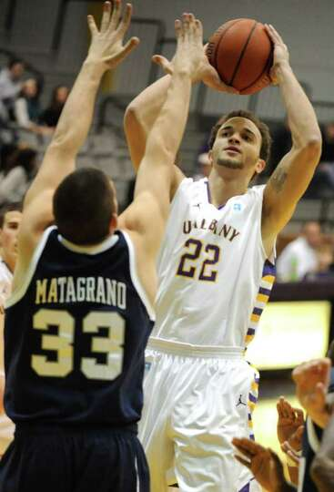 Ralph Watts of UAlbany is guarded by Chris Matagrano of New Hampshire as he goes up for two points d
