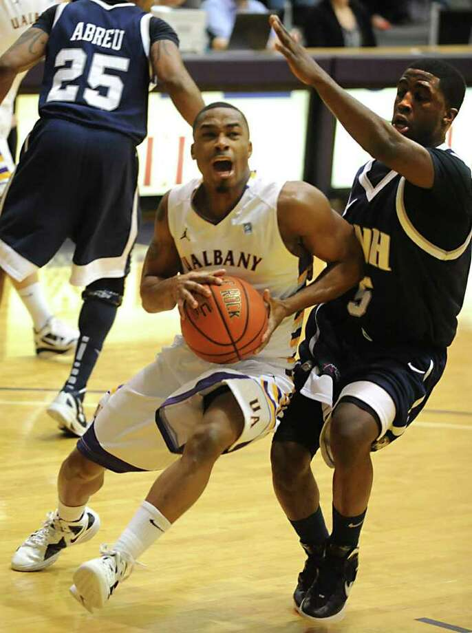 Mike Black of UAlbany is fouled by Jordon Bronner of New Hampshire as he drives to the basket during a basketball game on Wednesday, Jan. 11, 2012 at SEFCU Arena in Albany, N.Y.  (Lori Van Buren / Times Union) Photo: Lori Van Buren