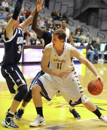 Luke Devlin of UAlbany is double teamed as he drives to the basket during a basketball game against